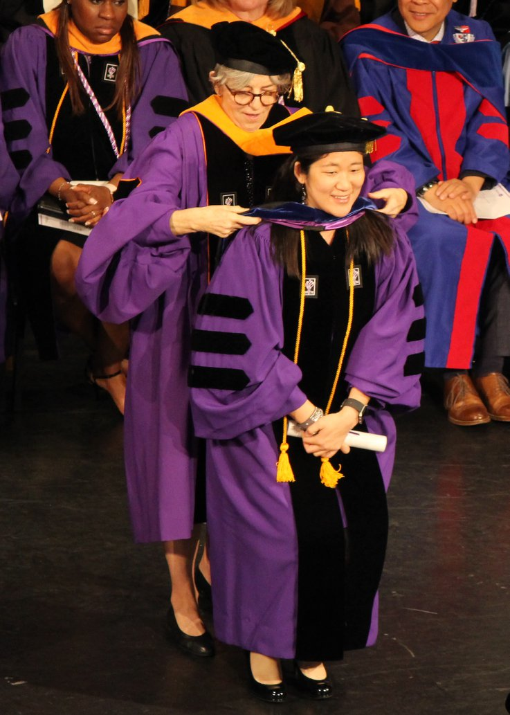 PhD graduate Jin Jun being hooded at graduation
